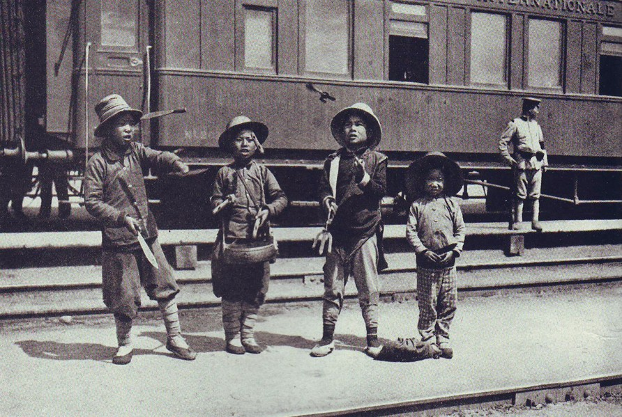 Мальчишки жонглеры, выступающие перед пассажирами па ж/д платформе